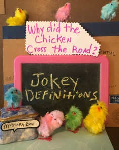 Fuzzy Chickens gathered around pink framed chalk board that says Jokey Definitions. Small glass Mystery Box on lower left is blue and white, edged in goldgold